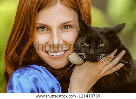 Red-haired smiling beautiful young woman in blue blouse with black cat, against green of summer park. - stock photo