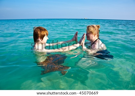 red haired woman and son are enjoying the beautiful clean sea and having fun