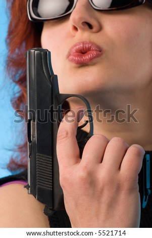 red haired woman holding a pistol. fine-art close-up portrait on blue background - stock photo