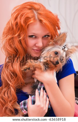 Red-haired woman in blue clothes is holding a little dog