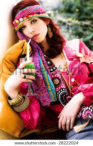 red haired woman in colorful clothes drinking juice on terrace - stock photo