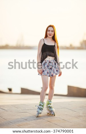 red-haired woman in roller skate in a city park on her T-shirt and bright blue chert in the park grow spruce lined road pavement - stock photo