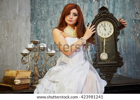 Red-haired woman in white dress sits on old grand piano lid holding pendulum clock. - stock photo