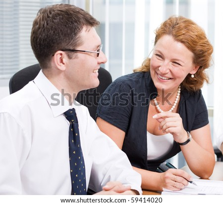 Red-haired woman laughing to his business colleague during meeting in Hi Res. Handsome man laughing to her and listening to her very attentively. - stock photo