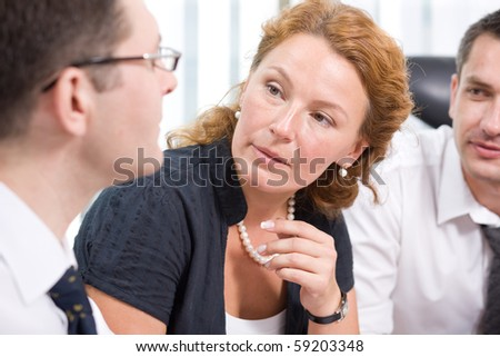 Red-haired woman listening to his colleague during meeting in Hi Res. People sitting at the table and discussing several burning issues indoors. - stock photo