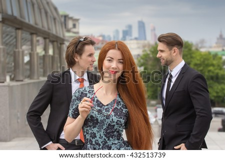Red-haired woman posing on two businessman on background - stock photo
