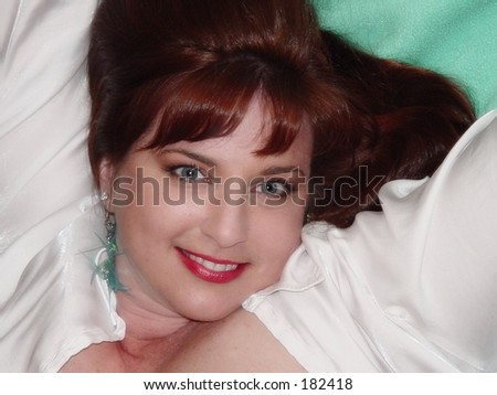 Red haired woman reclining in white satin shirt against green background - stock photo