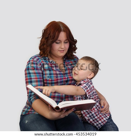 Red haired woman sits together with little boy reading a big book - Mother and little son on gray background in square - Education inside family - stock photo