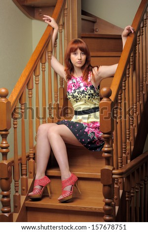 Red haired woman sitting on wooden stairs indoor - stock photo