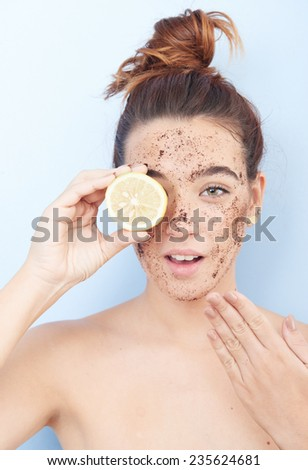 Red-haired woman with a scrub applied  and a slice of lemon  - stock photo