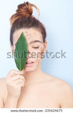 Red-haired woman with a scrub applied and sheet covering her face - stock photo