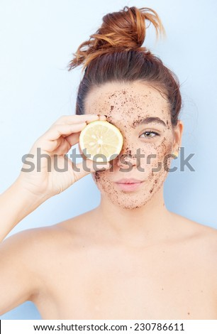 Red-haired woman with a scrub applied to her face and a slice of lemon covering face - stock photo
