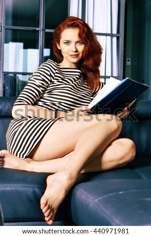 Red-haired young business woman or student girl working with documents at indoor. Modern lifestyle concept.