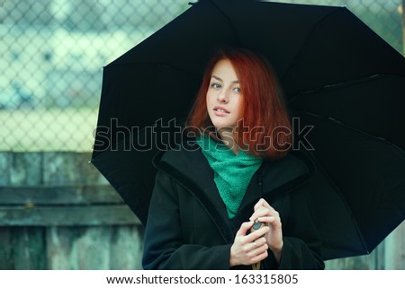 red-haired young girl with an umbrella on a cloudy day - stock photo