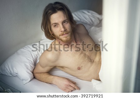red-haired young man with naked upper body lying in bed