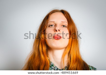 red-haired young woman showing tongue