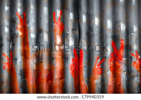 Red hand prints making peace signs on a metal wall - stock photo