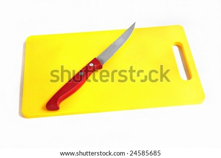 Red handled knife on a bright yellow chopping board - stock photo