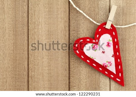 Red handmade felt heart clipped with a clothespin to clothes line on wooden background - stock photo