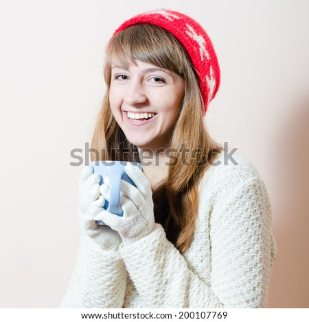 Red hat & cup: portrait of pretty girl in knitted gloves and cap with a pattern snowflakes, white sweater having fun drink beverage happy smiling & looking at camera on light copy space background - stock photo