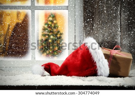 red hat on window sill and gift  - stock photo