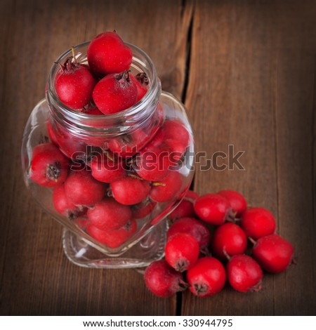 Red hawthorn berries in a glass jar  on wooden background