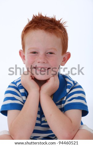 Red head boy wearing blue striped shirt with happy and smiling expression on face