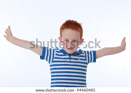 Red head boy wearing blue striped shirt with happy expression on face - stock photo