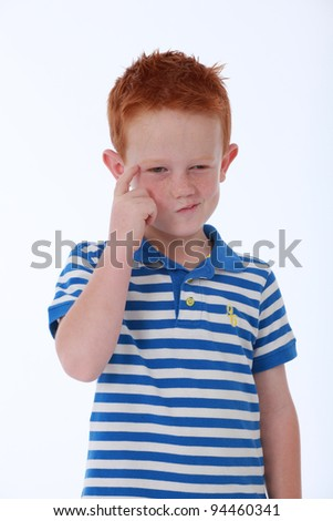 Red head boy wearing blue striped shirt with thinking expression on face - stock photo