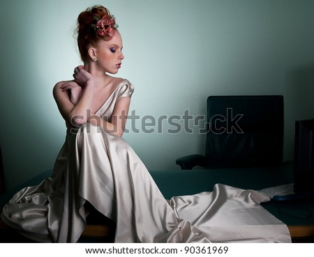 Red head freckled young woman in office space sitting on secretary desk - stock photo