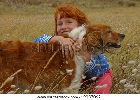 Red headed girl with red haired dog among bunny tails grasses in a beach side meadow - stock photo