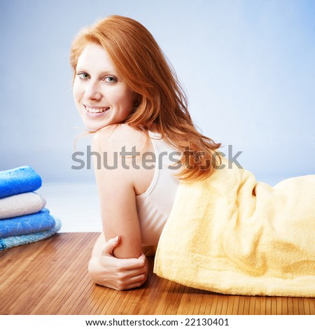 Red headed woman in towel lying on wooden floor and smiling - stock photo