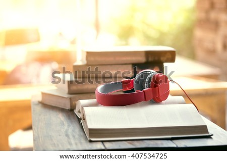 Red headphone on book in cafe or library,morning light. - stock photo