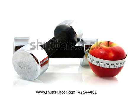 red healthy apple with measure tape and dumbbells for training - stock photo