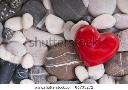Red heart among river pebble stones - stock photo