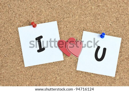 Red heart and a slip of paper with the words i love you on cork board background - stock photo