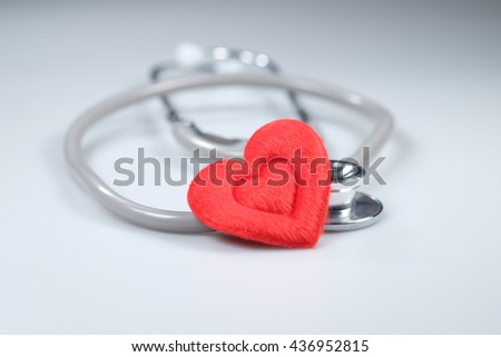 Red heart and a stethoscope isolated on white background - stock photo