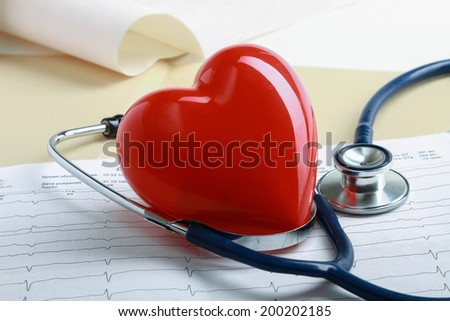 Red heart and a stethoscope on cardiagram - stock photo