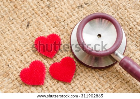 Red heart and a stethoscope on sack background. - stock photo