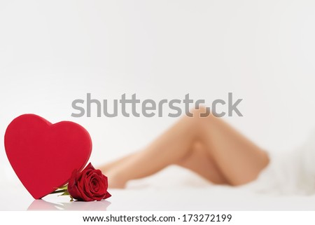 red heart and a wet red rose in front of beautiful legs from a woman - stock photo