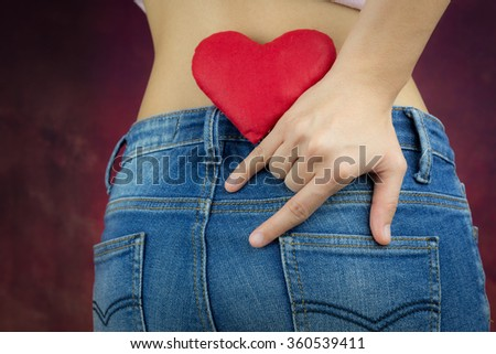red heart and finger gesture of love by woman shot from her back of the hip, valentine's concept