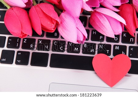 Red heart and flowers on computer keyboard close up