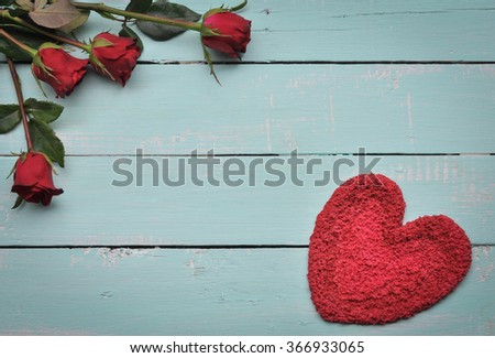Red heart and roses on the wooden background.
