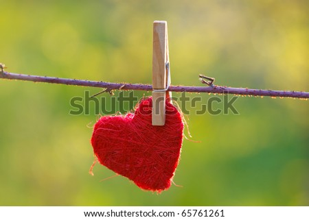 Red heart attached to a clothesline with pin - stock photo