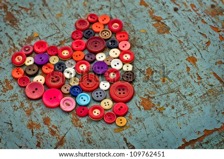 Red heart background on vintage old surface.Old colorful buttons/Valentines day background - stock photo