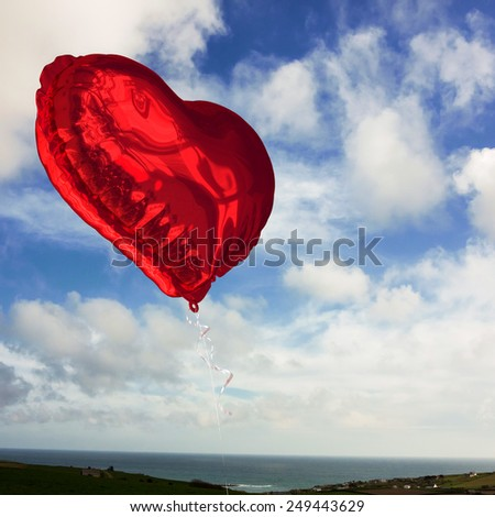 Red heart balloon against blue sky with white clouds - stock photo