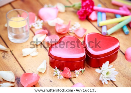 Red heart box with flower petals decorative on wooden table. background for valentines day concept
