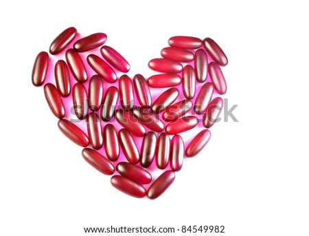 Red heart by pill isolated on white background - stock photo