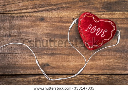red heart & earphone on old wood for music lover concept background - stock photo
