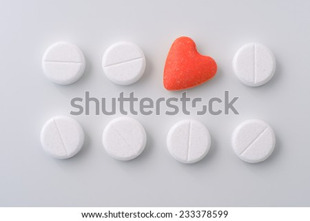Red heart form pill surrounded by white pills. Pills of love. - stock photo